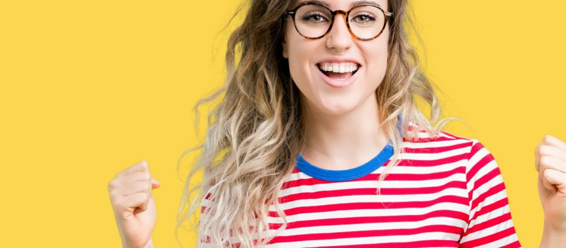 Beautiful young blonde woman wearing glasses over isolated background celebrating surprised and amazed for success with arms raised and open eyes. Winner concept.