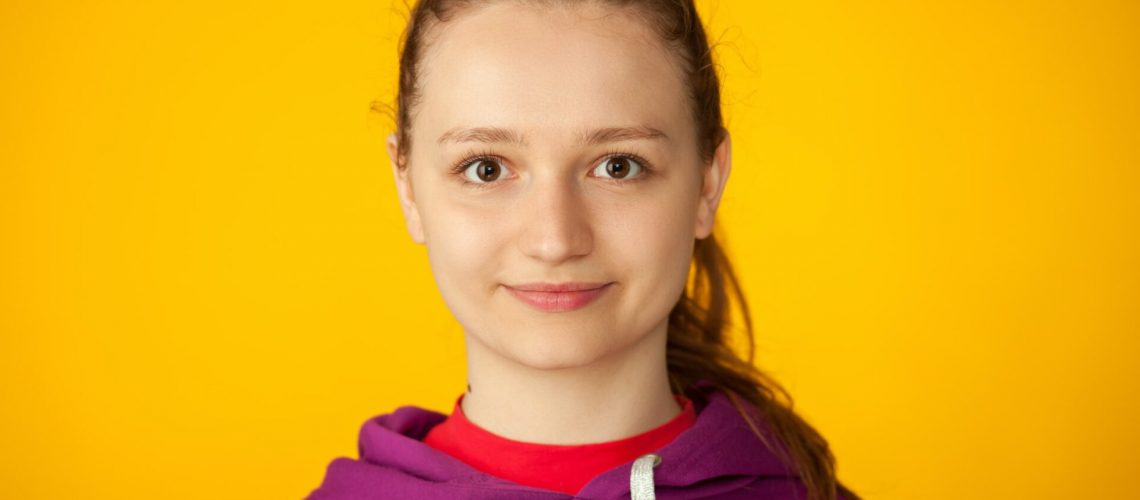Studio portrait of an attractive 18 year old woman on yellow background
