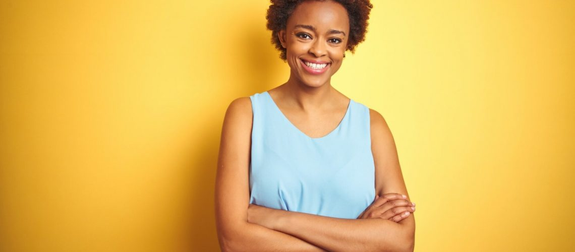 Beautiful african american woman wearing elegant shirt over isolated yellow background happy face smiling with crossed arms looking at the camera. Positive person.