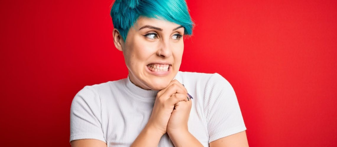 Young beautiful woman with blue fashion hair wearing casual t-shirt over red background laughing nervous and excited with hands on chin looking to the side