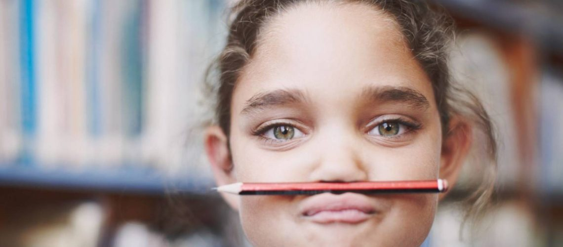 A cute young girl balancing her pencil on her lips and pulling a face