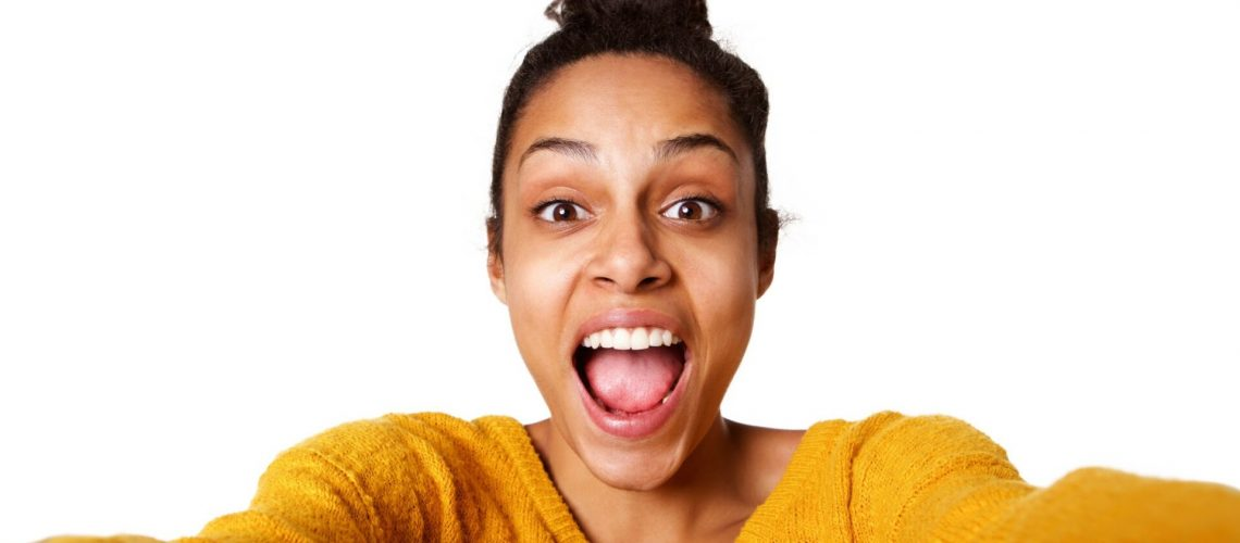 Close up portrait of excited young african lady taking selfie and laughing on white background