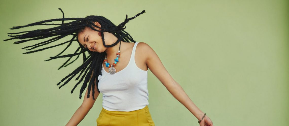 Studio shot of an attractive young woman tossing her hair against a green background
