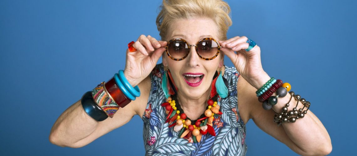 Summer portrait of creative, colorful senior woman against blue background. Studio shot.